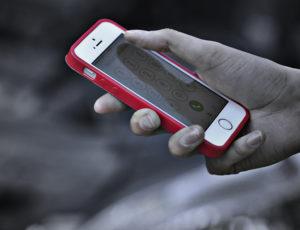 片手にスマートフォン持つ人の手