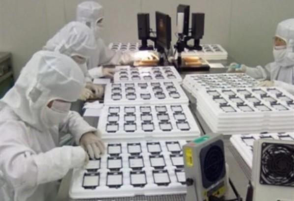 工場で厳しいチェックをする人とiPhoneのパネル